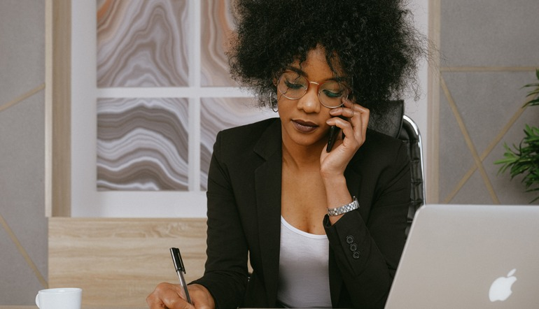 Woman in black blazer holding smartphone